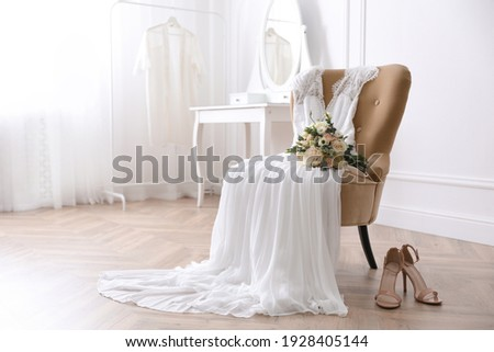 Elegant wedding dress, shoes and bouquet in room Royalty-Free Stock Photo #1928405144
