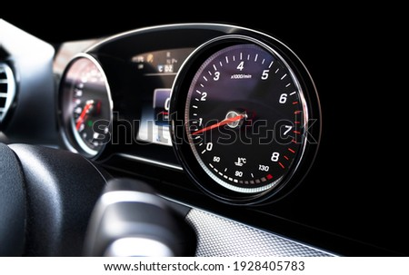 Close up shot of a speedometer in a car. Car dashboard. Dashboard details with indication lamps. Car instrument panel. Dashboard with speedometer, tachometer, odometer. Car detailing. Royalty-Free Stock Photo #1928405783