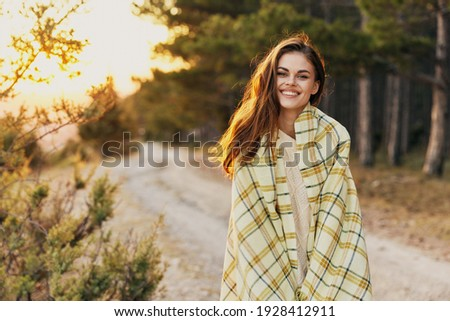 woman near coniferous forest road plaid sunset Royalty-Free Stock Photo #1928412911