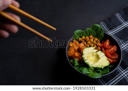 Eating with chopsticks avocado vegan buddha bowl with cherry tomatoes and spinach.Closeup view of healthy homemade food on dark background.