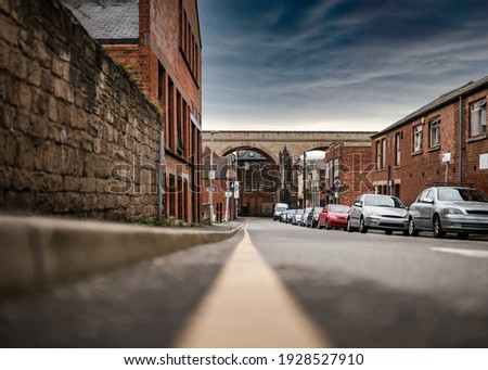 No parking restrictions yellow line on road low angle showing cars parked on busy town street scene. Railway arches bridge shops and houses and dramatic storm sky. Royalty-Free Stock Photo #1928527910
