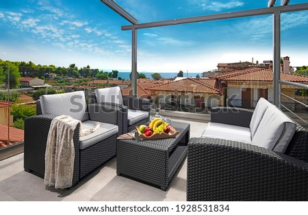 Recreation concept panorama of modern patio with wicker grey rattan furniture. Contemporary armchairs, couch, table on roof top terrace of luxury sea view resort in old European city Royalty-Free Stock Photo #1928531834