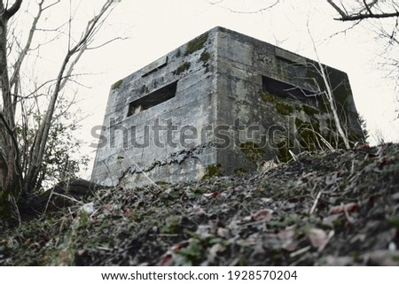 A brutalist cold gritty concrete world war two, ww2 pillbox war bunker defence fortress in a dirty forgotten woodland in europe. wartime relics and forgotten outpost using solid architecture to defenD Royalty-Free Stock Photo #1928570204