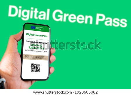 The digital green pass of the EU with the QR code on the screen of a mobile held by a hand with a blurred green background. Immunity from Covid-19. Permit to travel without restrictions in Europe.