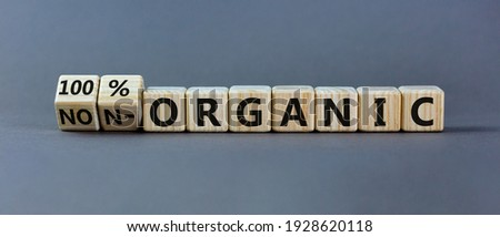 100 percent organic symbol. Fliped wooden cubes and changed words non-organic to 100 percent organic. Beautiful grey background, copy space. Business, healthy lifestyle 100 percent organic concept. Royalty-Free Stock Photo #1928620118