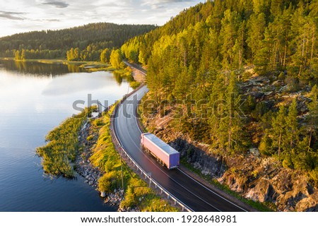 Aerial view of semi truck with cargo trailer on road curve at lake shore with green pine forest. Transportation background. Beautiful nature landscape at sunset in Republic of Karelia, Russia Royalty-Free Stock Photo #1928648981