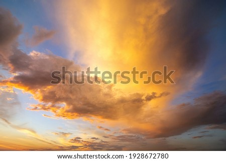 Dramatic yellow sunset landscape with puffy clouds lit by orange setting sun and blue sky. Royalty-Free Stock Photo #1928672780