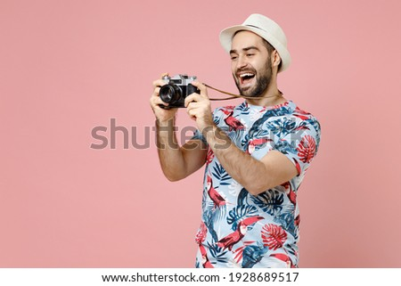 Funny young traveler tourist man in summer clothes hat taking pictures on retro vintage photo camera isolated on pink background studio. Passenger traveling on weekends. Air flight journey concept