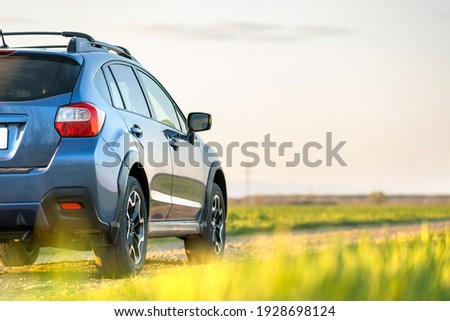 Landscape with blue off road car on gravel road. Traveling by auto, adventure in wildlife, expedition or extreme travel on a SUV automobile. Offroad 4x4 vehicle in field at sunrise. Royalty-Free Stock Photo #1928698124