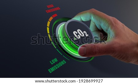 Lower CO2 emissions to limit global warming and climate change. Concept with manager hand turning knob to reduce levels of CO2. New technology to decarbonize industry, energy and transport Royalty-Free Stock Photo #1928699927