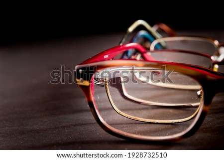 Multiple pairs of eyeglasses on a black surface. Only one half of the glasses are visible. The glasses are nested within each other and are visible through the lens of each pair. Royalty-Free Stock Photo #1928732510