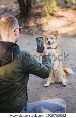 youg man taking a photo of his welsh corgi pembroke dog