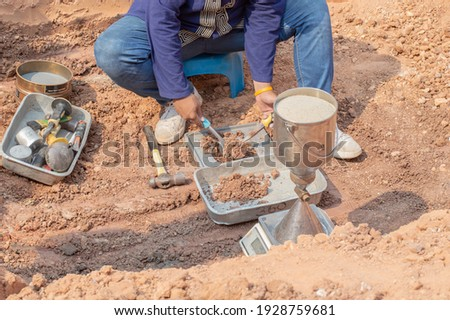 Worker using equipment for testing laboratory field density test sand cone method and soil density test of road under the construction. Royalty-Free Stock Photo #1928759681