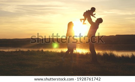 Child in the hands of parents jumps from dad to mom and laughs. Happy family walk on the beach at sunset. Child, daughter, mom, dad play fun in park in park in sun. Family fantasies, childhood dreams. Royalty-Free Stock Photo #1928761742