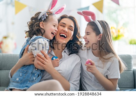 Happy holiday! Mother and her daughters with painting eggs. Family celebrating Easter. Cute little children girls are wearing bunny ears.  Royalty-Free Stock Photo #1928848634