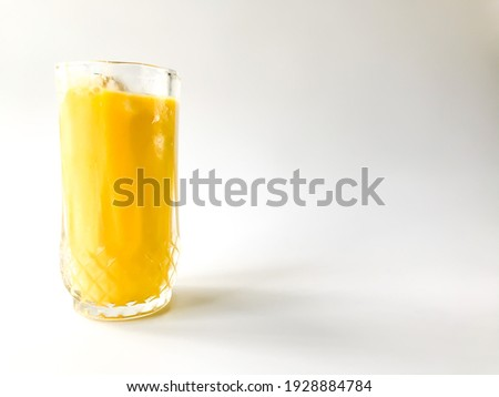 Selective focus of Mango Juice in a premium glass isolated on white background with a blank for writing. Fresh juice background.