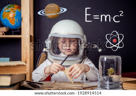 Child dreams about future of planet. Portrait of young scientist with magnifying glass. Success, creative and startup concept. Space knowledge about planets and planets. Copy space for your text.