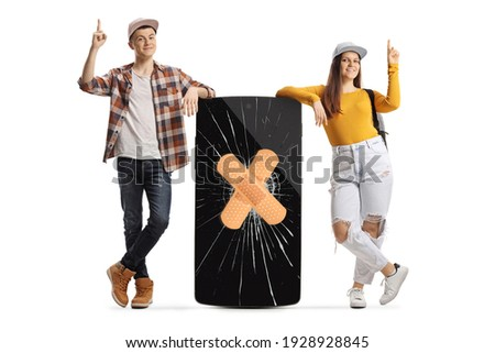 Full length portrait of male and female students leaning on a mobile phone with cracked screen and bandage and pointing up isolated on white background