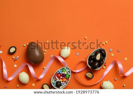 Easter chocolate eggs, candies and sprinkles on orange background Royalty-Free Stock Photo #1928973776