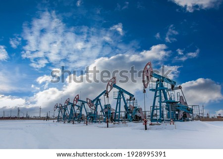 Oil pump jack under the blue sky with clouds winter working. Oil rig energy industrial machine for petroleum in the sunset background for design. Nodding donkey