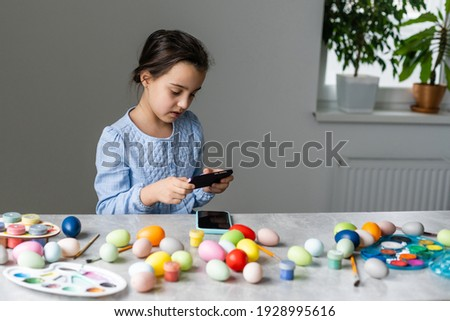 little girl takes pictures of painted eggs and paints