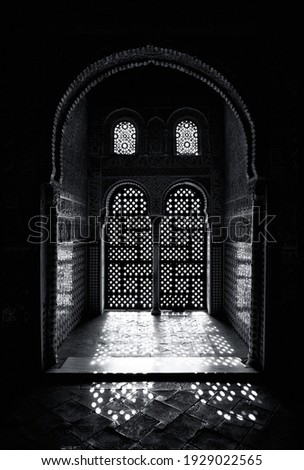 Arabesque style ornate window detail, with sunlight shining through. Black and white.  Royalty-Free Stock Photo #1929022565