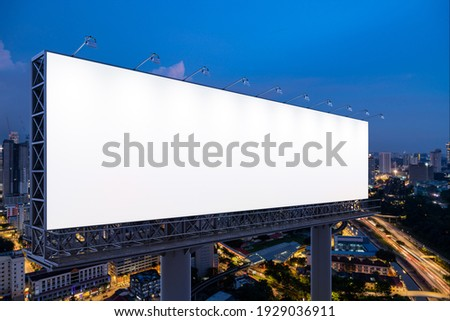 Blank white road billboard with KL cityscape background at night time. Street advertising poster, mock up, 3D rendering. Side view. The concept of marketing communication to promote or sell idea.