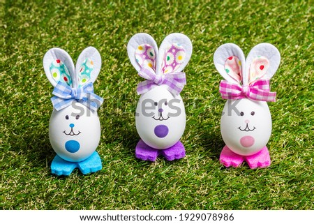 Traditional Easter festive concept. Multicolored cute handmade rabbits from eggs on green grass background, copy space