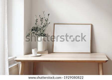Home office concept. Empty horizontal wooden picture frame mockup. Cup of coffee on wooden table. White wall background. Vase with olive branches. Elegant working space. Scandinavian interior design. Royalty-Free Stock Photo #1929080822