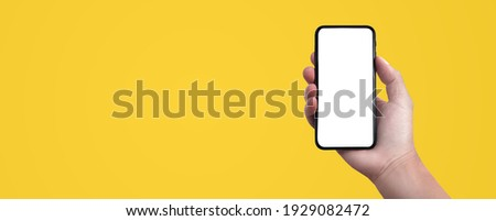 Blank screen of Mobile phone with Hand holding on solid color background. of free space for your copy, view from top. Creativity ideas concept.