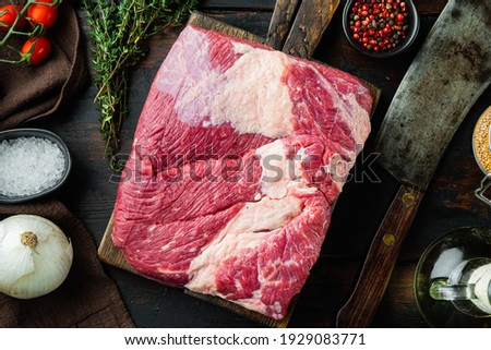 A whole piece of raw Beef Brisket set,with ingredients for smoking making barbecue, pastrami, cure, on old dark wooden table background, top view flat lay Royalty-Free Stock Photo #1929083771