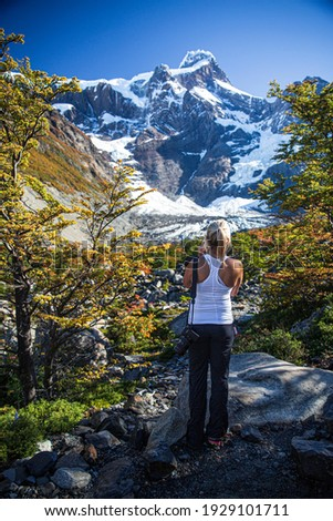 A woman taking pictures while hiking.