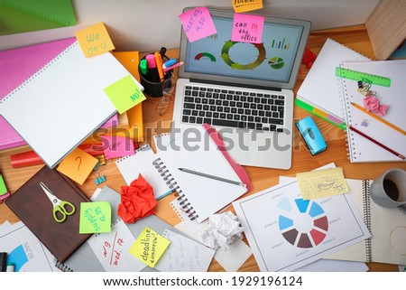 Messy table with laptop and sticky notes, above view. Concept of being overwhelmed by work Royalty-Free Stock Photo #1929196124