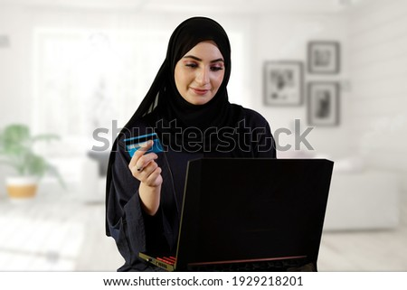 Woman buying online eCommerce website doing shopping while paying with a credit card. Arab Emirati wearing Abaya Hijab doing web purchase Royalty-Free Stock Photo #1929218201