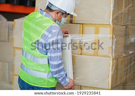 close up view of man worker wearing protective face mask and safety suite wrapping stretch film parcel on pallet in factory warehouse, logistic industry concept.  Royalty-Free Stock Photo #1929235841