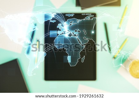 Abstract graphic digital world map with connections and modern digital tablet on desktop on background, top view, globalization concept. Multiexposure