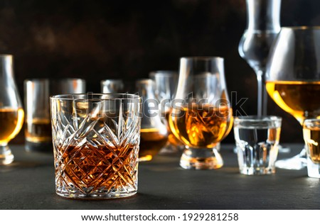 Hard strong alcoholic drinks and distillates in glasses in assortment: vodka, cognac, tequila, scotch, brandy and whiskey, grappa, liqueur, vermouth, tincture, rum. Brown background Royalty-Free Stock Photo #1929281258