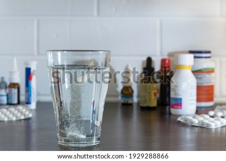 Tablets are dissolved in a glass of water against the background of tablets and medicines. Water poured into a glass with medicine. Throw the pills in the water.