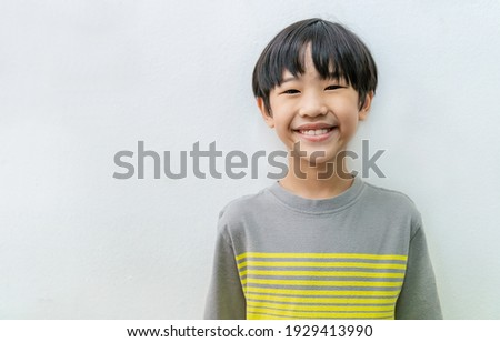 Portrait of beautiful positive asian little boy - close up portrait of asian Japanese toddler boy. Happy handsome nerd student male wear t-shirt with big smile isolated on white background.