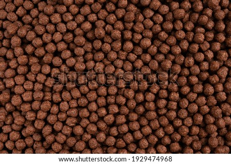 Chocolate breakfast cereal texture. Cereal balls as background. Chocolate corn balls. Top view. Royalty-Free Stock Photo #1929474968