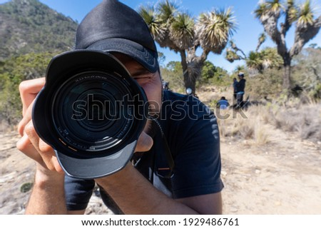 Male photographer holding the camera to the face standing on the hill against the mountains