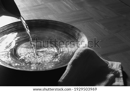 Pitcher pouring water into basin with linen cloth Royalty-Free Stock Photo #1929503969