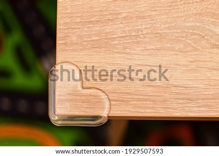 Safety soft silicone pads on the corners of the rounded shape. They cover sharp corners in the house, protecting the child from injury. Parents care for the baby. Heart-shaped safe corners Royalty-Free Stock Photo #1929507593