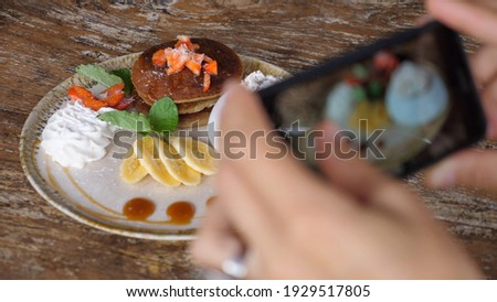 Hands taking pictures of healthy vegan breakfast of pancakes and fruits served on a wooden table