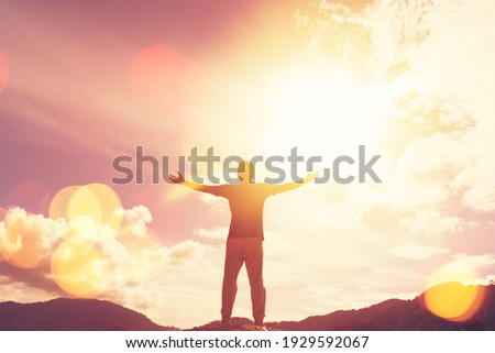 Copy space of man hand raising on top of mountain and sunset sky abstract background. Freedom travel adventure and business victory concept. Vintage tone filter effect color style. Royalty-Free Stock Photo #1929592067