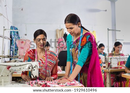 Senior inspector explaining women textile worker sewing garment on production line Royalty-Free Stock Photo #1929610496