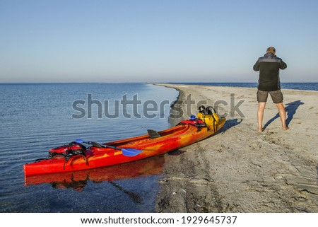 A male standing next to his kayak and taking a picture of the beautiful seascape in Kuznica, Poland