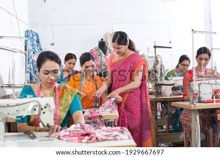 Woman textile worker checking garment stock at factory Royalty-Free Stock Photo #1929667697