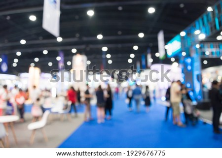 Abstract blur people in exhibition hall event trade show expo background. Large international exhibition, convention center, business marketing and event fair organizer concept. Royalty-Free Stock Photo #1929676775