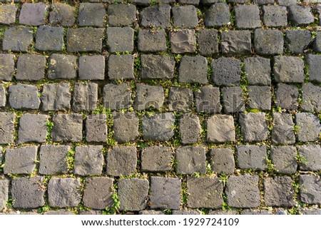 Black gray basalt lava rectangular pavement cobblestones in square format texture. Basalt lava paving stones textures. Royalty-Free Stock Photo #1929724109